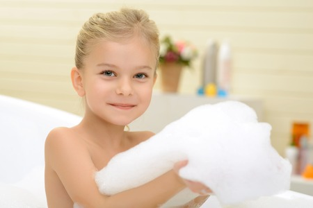 woman bath: Like taking bath. Little cheerful pretty girl sitting in the bath tube and expressing joy while playing with foam