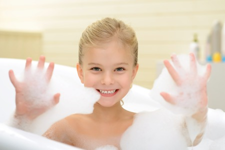 woman in bath: Joyful mood. Pleasant smiling little girl playing with foam and resting while taking bath