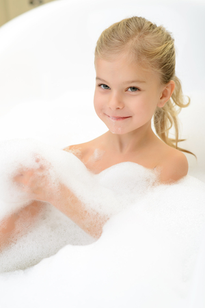 woman in bath: Take care of yourself. Pleasant content little girl lying in the bath tube and feeling happy while taking bath