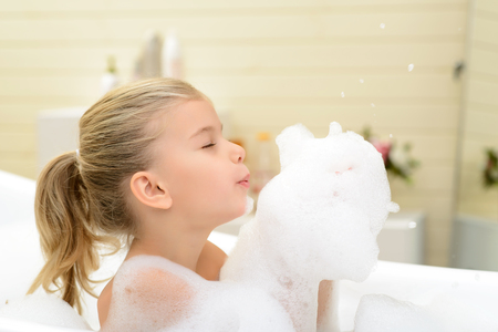 woman bath: Full of joy. Pretty little girl holding foam in her hands and blowing on it while taking bath