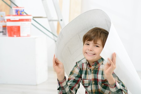 In a shelter. Cheerful positive little boy holding plan of his house and hiding under it while playing Stock Photo