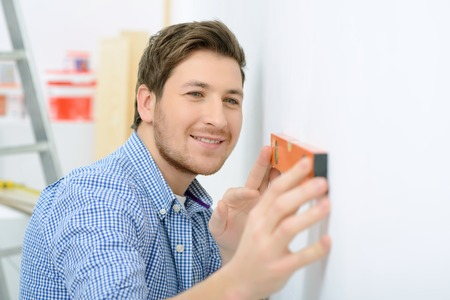 to be pleasant: Be accurate. Close up of pleasant smiling man holding spirit level on the wall and making measurements while doing renovation