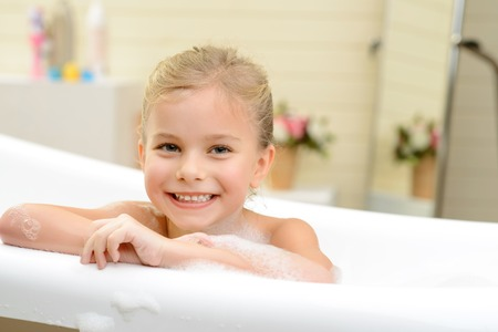 woman in bath: Full of happiness. Close up of cute cheerful little girl folding her hands and smiling while taking bath Stock Photo