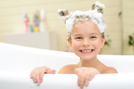 woman in bath: Play with me. Content cheerful little girl sitting in the bath tube and smiling while having fun