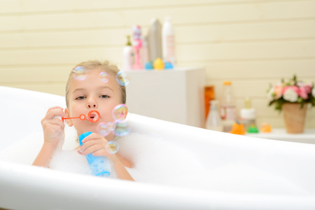 woman in bath: Happy childhood. Pleasant playful little girl blowing soap bubbles and having fun while taking bath Stock Photo