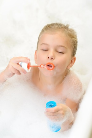 closing time: Time for fun. Top view of pretty little girl closing her eyes and blowing soap bubbles while taking bath Stock Photo