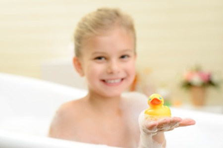 woman in bath: We are best friends. Pleasant smiling little girl sitting in the bath tube and holding rubber duck while taking bath
