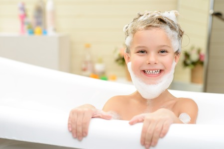 woman in bath: Lets play. Cheerful content little girl sitting in the bath tube and having fun while washing her hair