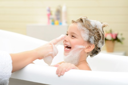 Joyful moment. Cute smiling little girl sitting in the bath tube and taking bath while having fun with her mother