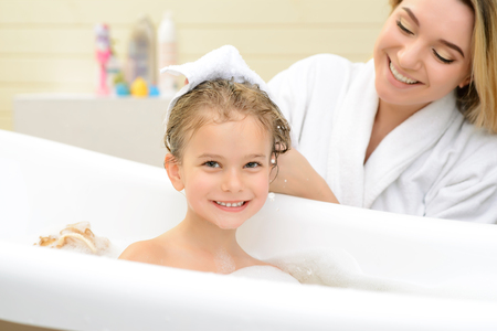 Happy together. Pleasant cute little girl sitting in the bath while her mother drying her hair with towel