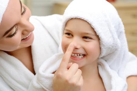 ねえ。楽しい笑顔の娘とお風呂の後で一緒に楽しんで愛する母のクローズ アップ