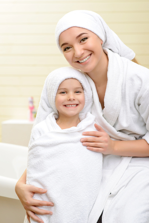 taking shower: Happy family. Pleasant mother and daughter smiling and bonding to each other after taking shower