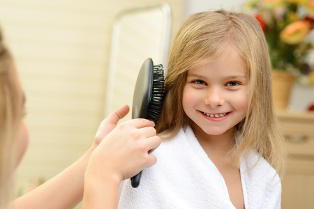 Little daughter. Pleasant smiling pretty girl smiling while her mother brushing her hair