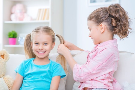 upbeat: Happy together. Upbeat cheerful little girl making hairstyle to her sister while playing on the sofa and feeling content