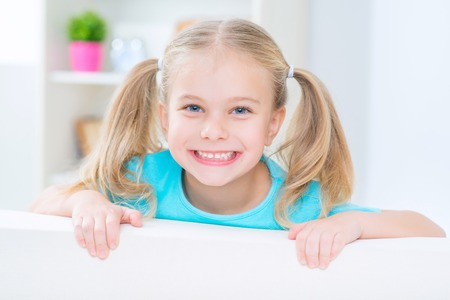 Nice day. Pleasant overjoyed little girl hiding behind the sofa and smiling while having fun at home Stock Photo