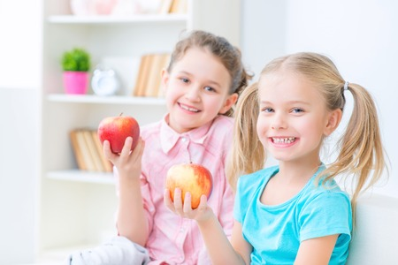 keeps: Apple a day keeps doctor away. Cheerful pretty little girls holding apples and feeling delighted while having fun together