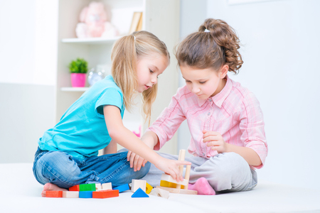 erector: Favorite game. Pleasant cute little sister sitting on the floor and playing with erector set while having fun together