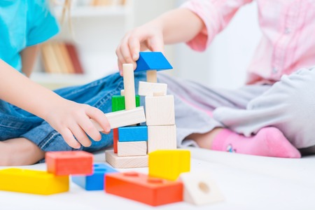 erector: Childish game. Close up of erector set lying on the floor while little sisters playing with it at home Stock Photo