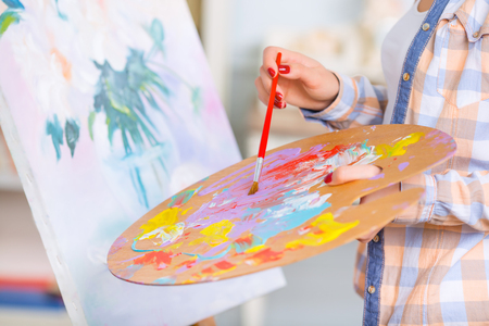 Gifted painter. Young girl is occupied with painting a picture. Stock fotó
