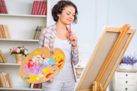 visual therapy: Painting process. Young attractive woman is thoughtfully looking at her unfinished piece of art. Stock Photo