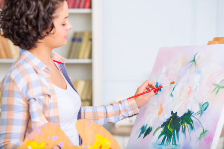 visual therapy: Piece of art. Young attractive woman is standing and oil painting a beautiful artwork.