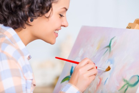 artwork: Almost done. Young attractive woman is finishing beautiful artwork. Stock Photo