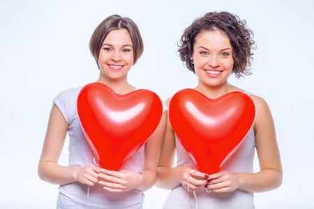 kinfolk: Friendly sisters. Two young cheerful sisters are holding heart-shaped balloons in their hands.
