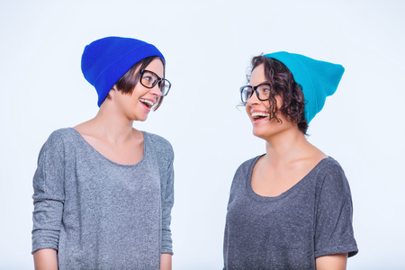 alike: Acting alike. Two young cheering sisters are wearing same hats and glasses.