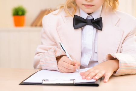 filling out: Busy girl. Little girl is sitting at the desk and diligently filling out a paper.