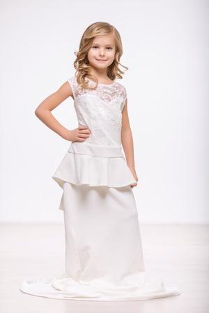 petite fille avec robe: Voulez-vous �pouser. pleine longueur d'agr�able petite fille tenant sa main sur la ligne de taille et exprimant la joie tout debout isol� sur fond blanc dans une robe de mari�e Banque d'images