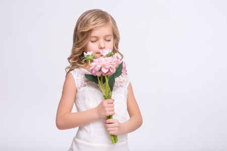 unforgettable: Unforgettable scent. Cute beautiful little girl holding bouquet of flower while feeling the aroma