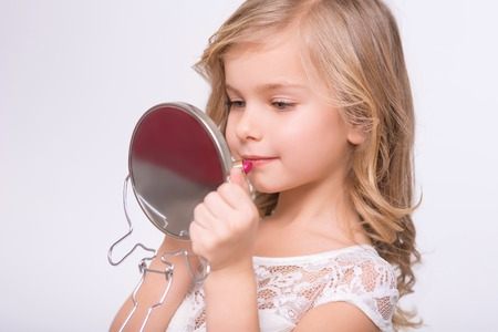 lip stick: Beautiful lady. Close up of pleasant little girl holding lipstick and mirror while doing make up Stock Photo