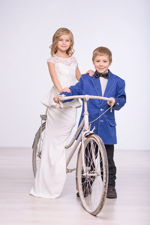 Have fun together. Pleasant joyful little boy holding bicycle and riding with her wife while having wedding 版權商用圖片