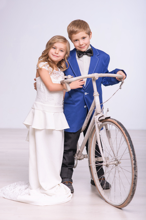Love in the air. Happy content little couple holding bicycle while celebrating wedding
