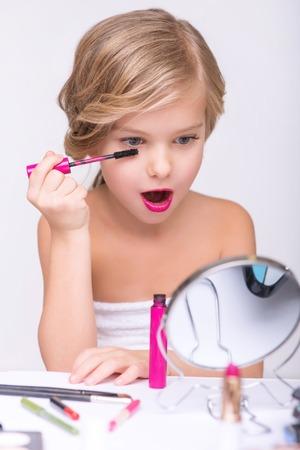 bid: Lo pestañas oferta. Agradable niña sorprendió sentado en la mesa y mirando en un espejo mientras haciendo hacer Foto de archivo