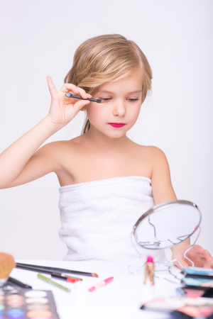 to be pleasant: Want to be beautiful. Pleasant concentrated little girl holding brush and doing make up while sitting at the table