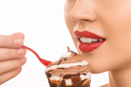 womanhood: Ice cream tasting. Young attractive girl wearing red lipstick is eating ice cream with plastic spoon. Stock Photo
