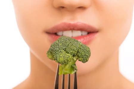 Healthy eating. Young attractive girl is holding broccoli on fork in front of her mouth.