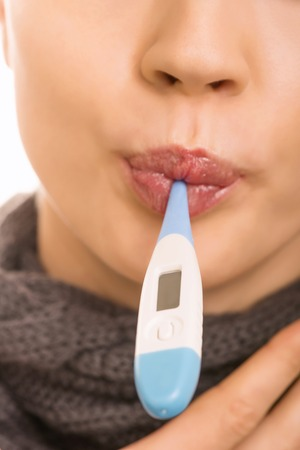 womanhood: Caught a cold. Young attractive girl is holding an oral thermometer in her mouth. Stock Photo