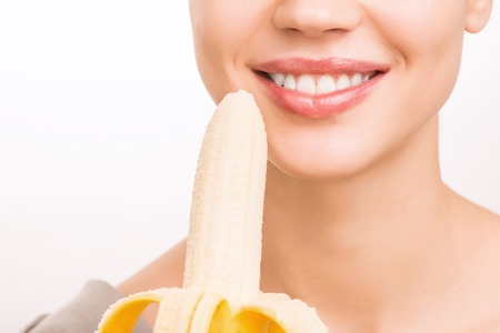 food stuff: Holding a banana. Young smiling girl is about to eat a banana.