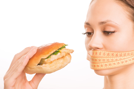 upholding: Hungry eyes. Young attractive girl taped with measuring strip upholding a burger and looking sad.