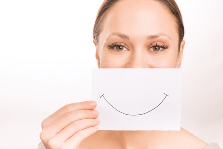 upholding: Smiley face. Young girl is upholding a smiley paper at her mouth.