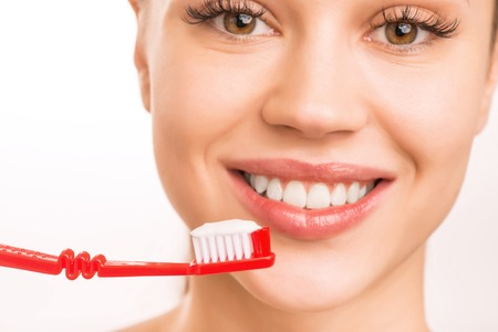 upholding: Mouth care. Young smiling girl is upholding a toothbrush with toothpaste on it.