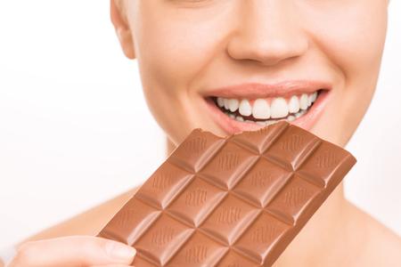 womanhood: Enjoyable food. Young attractive smiling girl is eating a chocolate bar Stock Photo