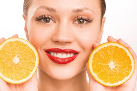 upholding: Girl and oranges. Young smiling attractive girl is upholding two halves of one orange beside her face. Stock Photo