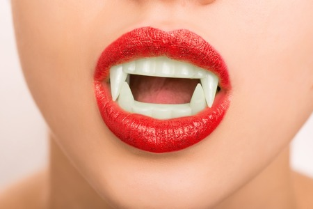 Vampire style. Young attractive girl is wearing sparkling red lipstick and fake vampire teeth.