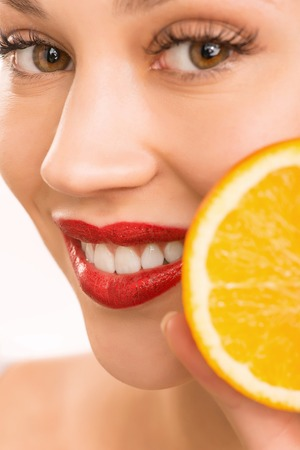 upholding: Posing with orange. Young attractive smiling girl is upholding an orange in front of her.