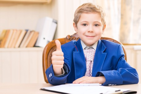 feeling up: Feeling optimistic. Little boy is smiling and showing thumbs up while sitting at the desk.