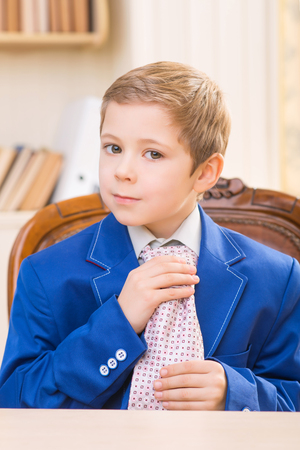 boyhood: Adjusting a tie. Small boy in businessman outfit adjusting big adult tie. Stock Photo