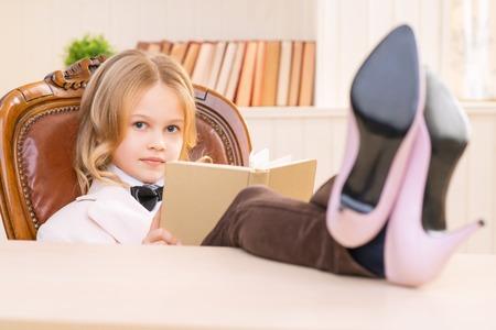 Ragazza con un libro. Pretty ragazza è seduta con le gambe in tacchi sulla scrivania e la lettura di un libro.
